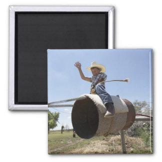 Boy (8-10) riding makeshift rodeo bull magnet