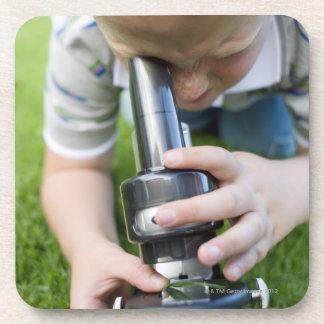 Boy (8-9) using light microscope, close-up coasters