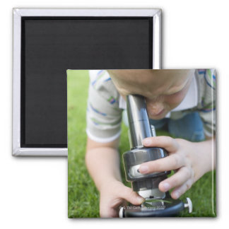Boy (8-9) using light microscope, close-up square magnet