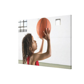 Boy aiming a shot with a basketball in a school canvas print