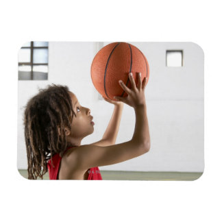 Boy aiming a shot with a basketball in a school magnet