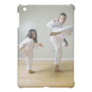 Boy and girl (4-9) practising Taekwondo kicks iPad Mini Cover