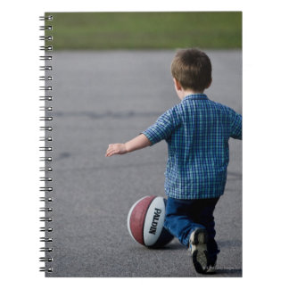 Boy chasing basketball outdoors notebooks