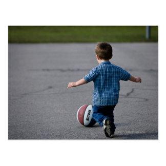 Boy chasing basketball outdoors postcard