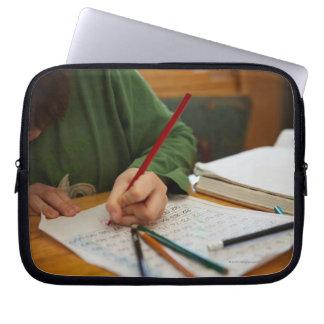 Boy concentrating on math homework laptop sleeve