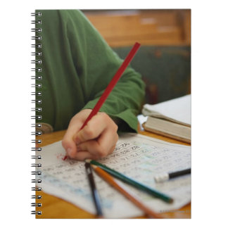 Boy concentrating on math homework spiral note book