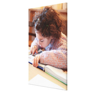 Boy concentrating on reading homework canvas print