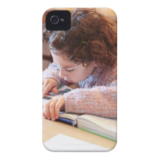 Boy concentrating on reading homework iPhone 4 Case-Mate cases