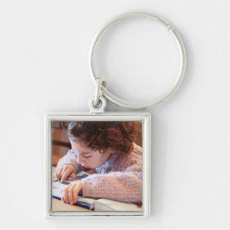 Boy concentrating on reading homework key ring