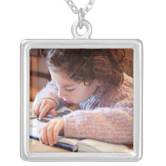 Boy concentrating on reading homework silver plated necklace