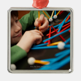 Boy connecting molecules for science project christmas ornament