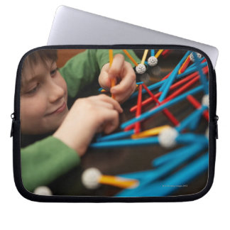 Boy connecting molecules for science project laptop sleeve