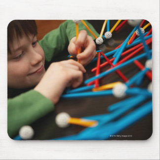 Boy connecting molecules for science project mouse mat