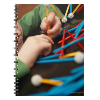 Boy connecting molecules for science project notebook