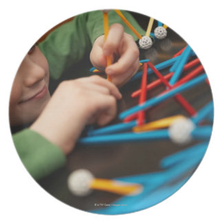 Boy connecting molecules for science project plate