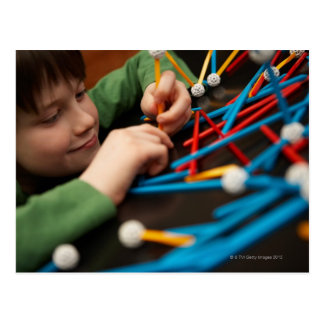 Boy connecting molecules for science project postcard