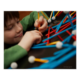 Boy connecting molecules for science project poster