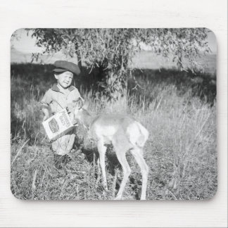 Boy feeding antelope by hand mouse mat