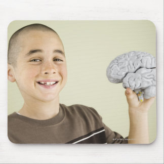 Boy holding human brain model mouse pad