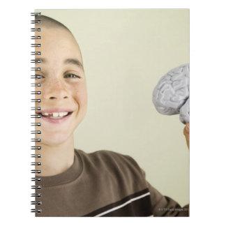 Boy holding human brain model notebook