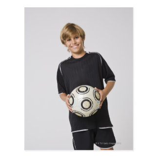 Boy holding soccer ball, smiling, portrait postcard