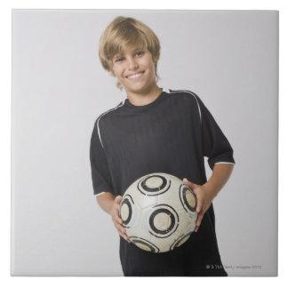 Boy holding soccer ball, smiling, portrait tile