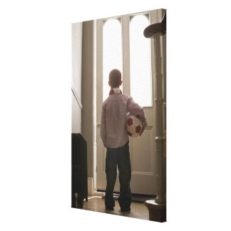 Boy in foyer with soccer ball canvas print