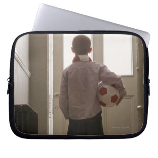 Boy in foyer with soccer ball laptop sleeve