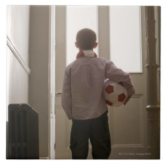 Boy in foyer with soccer ball tile