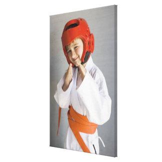 Boy in karate uniform wearing sparring headgear canvas print