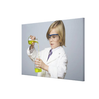 Boy pouring liquid into beaker stretched canvas print