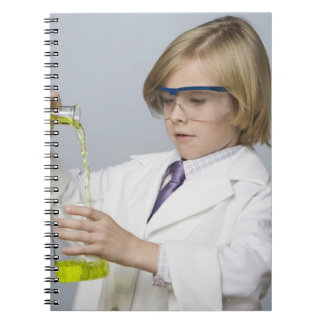 Boy pouring liquid into beaker notebooks