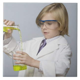 Boy pouring liquid into beaker tile
