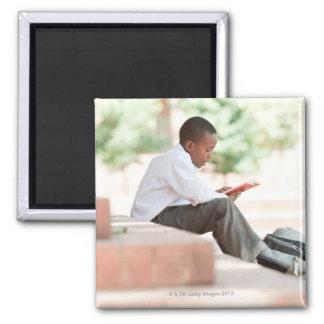 Boy reading on steps outside school, square magnet
