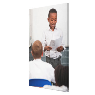 Boy standing in front of class reading in 2 stretched canvas print