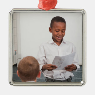 Boy standing in front of class reading in 2 christmas ornament