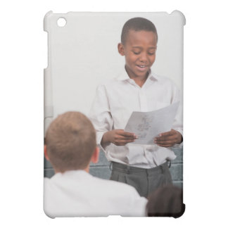 Boy standing in front of class reading in 2 cover for the iPad mini
