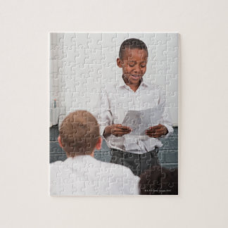 Boy standing in front of class reading in 2 jigsaw puzzle