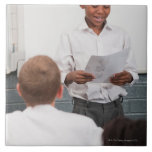 Boy standing in front of class reading in 2 large square tile
