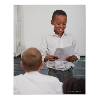 Boy standing in front of class reading in 2 print