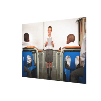 Boy standing in front of class reading in canvas print