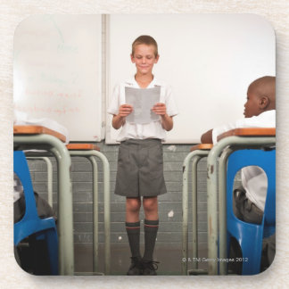 Boy standing in front of class reading in coaster
