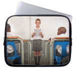 Boy standing in front of class reading in laptop sleeve
