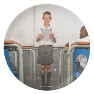 Boy standing in front of class reading in plates