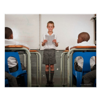 Boy standing in front of class reading in poster