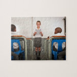 Boy standing in front of class reading in puzzles
