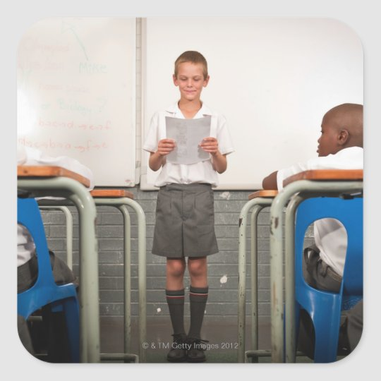 Boy standing in front of class reading in square sticker