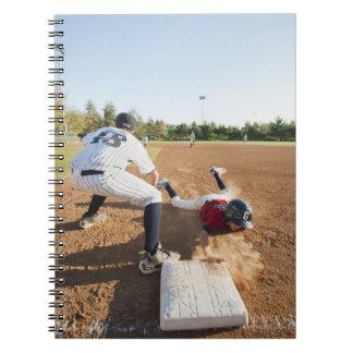Boys (10-11) playing baseball notebooks