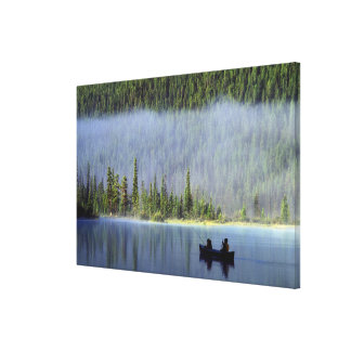 Boys fishing from canoe with mist in canvas print