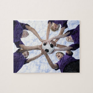 Boys holding soccer ball in huddle jigsaw puzzle